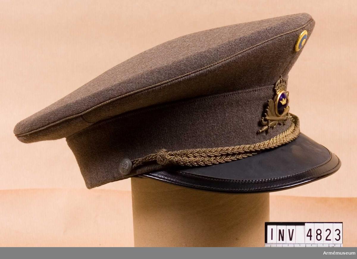 Gott skick. Storlek: 56. Tillverkad i platt typ av gråbrungrönt ylletyg och försedd med mössmärke m/1939 som utgöres av arméns emblem med korslagda svärd och krona jämte lagerkvistar i bronsfärgad metall med knapp m/1865 för officer. Upptill vid kullen neutralitetsmärket  m/1941 - användes 1939. Mössrem m/1939, flätad, bronsfärgad,  för regementsofficer samt knapp m/1939, liten, för mössremmens fästande. Mösskärm av svart lackerat läder utan särskild  beteckning. Tillverkare MEA, Stockholm.Mössan är buren av fältläkare Gerhard Rundberg.
