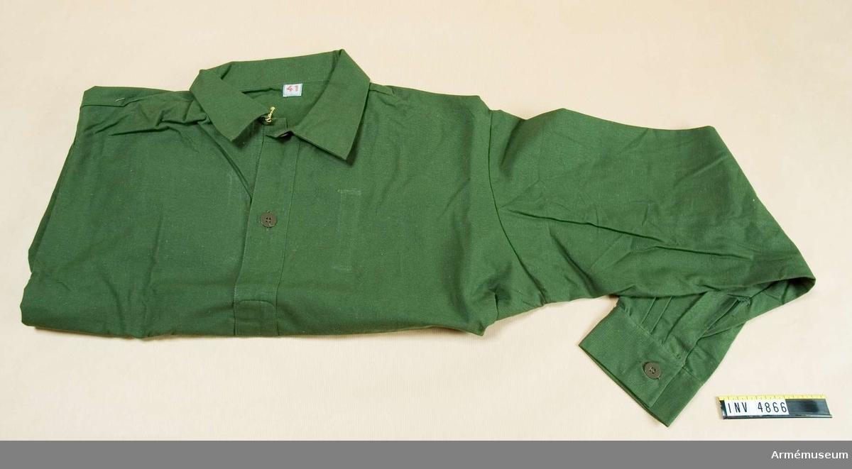 Storlek: 41.Fältskjorta, grön I 1. Med fast krage och sprund med krage och  enkel manschett. Används till fältuniform m/1958 och 1959. Tjänsteklass och tjänstegruppsbeteckning anbringas på vänster  sida av bröstet. UNIA 3:69-70.