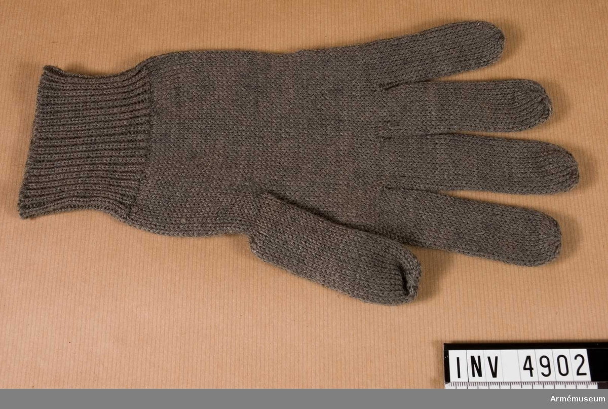 Stickad av gråbrungrönt yllegarn med muddar och alla fingrar fria.  Samhörande nr är AM.4860-4925