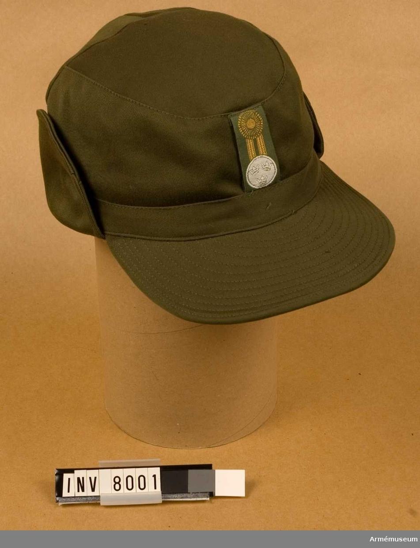 Tillverkad av olivgrönt tyg med mjuk skärm samt förses med invikbart pannskydd och utanpåliggande öron och nackskydd. Storlek 59. Nyskick 111.Har varit utställd på docka i Signalhallen men funnen omärkt då den togs ned ur montern.