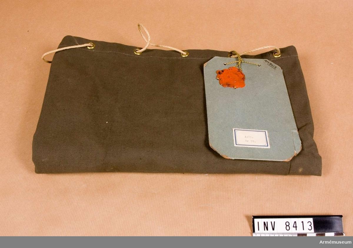 Av gråbrungrönt vindtyg med hål upptill för ihopdragning genomträdda med ett tvinnat snöre.  Vidhängande modellapp med beslut den 10 juni 1939 dnr 1576 utr.