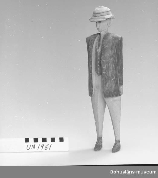 """Ur handskrivna katalogen 1957-1958: Träskulptur, förest. en europé. H. 33,2 cm. Mansfigur i kavajkostym och tropikhjälm. Hel. Infödingsarbete, Sydafrika.  Kompletterande uppgifter om UM001961 – UM001999: I arkivet finns korrespondens från maj 1927 mellan Ernst Nomell (Dulle[?]) och hans systrar rörande samlingen av skulpturer. Verifikationsnummer G:3:5.  Kopia i bilagepärmen. Lappkatalog: 9  I gåvobok finns upptaget en gåva till biblioteket på åtta böcker från Ernst Nomell, Kimberley: 1935, Port Elizabeth. Handbook for Visitors etc., Capetown;  1937, Kimberley. The City of Sunshine and Diamonds, Durban;  1938, Johannesburg. A Sunshine City built on Gold, Johannesburg 1931; 1939, Bloemfontein. Orange Free State, 1928, Bloemfontain; 1940, Durban. Official Guide Book, Durban; 1941, The Riviera of the South; 1942, Natal South Coast Visitors' Guide, 1929, Durban; 1943, Grahamstown, Bathurst and Port Alfred, 1928, Johannesburg.  I magasinet där naturhistoriska materialet förvaras låg en äldre maskinskriven solblekt papperslapp med följande text knappt skönjbar: """"En vacker samling MINERALER från AFRICA mm förärad till UDDEVALLA MUSEUM av Herr Ernst NOMELL N:o 5 Diebel Street, West end, Diamond Fields KIMBERLEY Transvaal Syd Africa."""" Var mineralerna finns återstår att undersöka. De är troligen inte katalogiserade under UM-nummer. /Marie Johansson, januari 2006.   Ernst William Nomell var ett av tio barn son till grosshandlarparet Johan August Nomell  och Elise, f. Kullgren i Uddevalla.  Han arbetade som ingenjör vid diamantbolaget De Beer i Kimberley."""