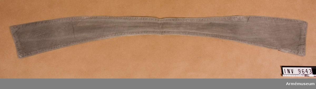 Sydd av gråbrungrönt bomullstyg, svängd och smalare mitt bak. På avigsidan en slå av tyget fastsydd på skrådden. Härigenom skall den motsvarande slipsänden träs.