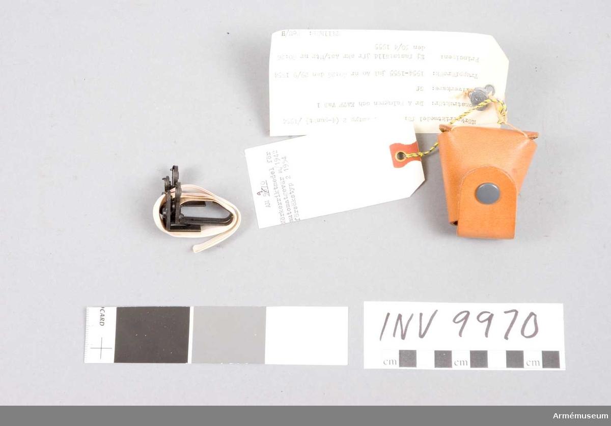 """Mörkerriktmedel t automatgevär m/1942.  Försökstyp 2, 4-punkt, 1954.Består av: 1 förvaringsask av papper märkt """"Ag 2"""", 1 korn, märkt """"Ag 2"""", 1 sikte, märkt """"Ag 2"""". 1 dubbelband av plast, l:580 mm, b:10 mm.Truppförsök: 1954-55 jml AO nr 60:26 den 29/9 1954. Principen: ej fastställd. Jfr skr Ast/Utr nr 60:26 den 30/4 1955. Tillhör: PcU/H.Blysigill, märkt """"AKGF"""" och en krona med två svärd i kors."""