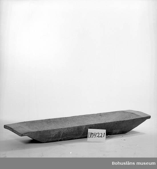 """Redskap/""""beredningskärl"""" vid bakning. Stort, rektangulärt och urholkat ur ett stycke. Kortsidorna smalnar av på höjden och bredden till ett tvärgående hand ytterst. Sprickor i botten samt vitnad inuti på grund av användning. Rinnmärken på utsidan.  Ur handskrivna katalogen 1957-1958: Stort baktråg L. 188 Br. 52,5, Av trä. Föremålet helt. Uddevalla"""