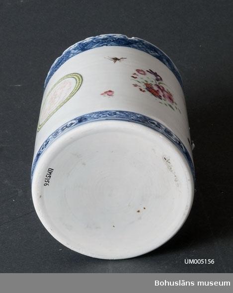 """Tillverkad i Kina. Cylindriskt kärl. Vit med blå mönsterbård i underglasyrdekor, i över- och nederkant. Ett monogram """"IG"""" vilket omfattas av en cirkel i grönt, svart och guld, är placerad mitt på muggen. Små handmålade blommor och insekter, oregelbundet placerade runt monogrammet. Hänkel saknas. Hänkel har haft fyra fästpunkter. Vid fästena är det blå blombuketter i relief. Många nagg vid mynningen.  Muggen är troligtvis tillverkad i Kina för en europeisk beställare.  Ölost (eller ölsupa, ölsoppa) är en traditionell bohuslänsk dryck som bygger på svagdricka och mjölk som kokas och vispas. Recept: Se UM005098  Hugo Hallgren var son till salteriidkaren och handelsmannen Johan Jacob Hallgren och Emelia Gerle. Företaget började sälja brissling på 1850-talet och 1864 startade man konservfabrik på Gullholmen som senare döptes till J. J. Hallgren & Söner. Sönerna var Gustav Richard, f. 1858 och Oscar Hugo, f. 1867.   Företaget introducerade flera nyheter inom ansjovisindustrin, bl.a. Sveriges första skinn- och benfria delikatessill. Man var också först med att lägga in ansjovis i hermetiskt slutna kärl av bleckplåt. 1898 köptes Hallgrens konservfabrik upp av det nybildade storföretaget AB Sveriges Förenade Konservfabriker (SFK). 1901 flyttade Hugo Hallgren till Ellös där han startade en ny konservfabrik.  För uppgifter om förvärvet, se UM005155  Ur handskrivna katalogen 1957-1958: Ölostmugg Mynningsdiam. 11,6. H.: 15,2. Vitt porslin med initialer och mönster i färg. Handtag saknas, något skadad.  Lappkatalog: 62"""
