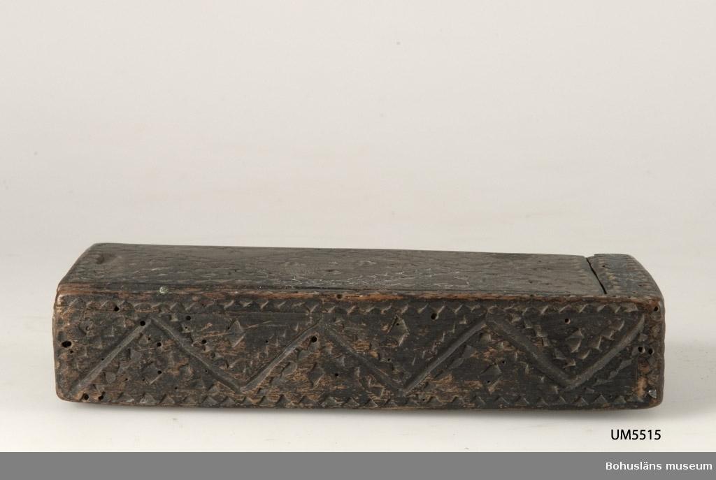 Rektangulär låda med skjutlock upptill. Ytan är täckt med geometrisk dekor bestående av uddsnitt. Inuti har den haft en skiljevägg och på så sätt har man kunnat välja om det skulle vara ett eller två fack. Är målad med mörkbrun färg. Skadedjursangrepp. Defekt långsida. Kan vara en raklåda.  Litt.; Gjaerder, Per, Esker og tiner, C. Huitfeldts förlag, Oslo, 1981, s. 48-50.  Ur handskrivna katalogen 1957-1958: Raklåda av trä Mått a) 18 x 7,5 x 3,5; locket b) 16,5 x 6,5 cm; m. skuren dekor; brunmålad. Trasig, maskäten.  Lappkatalog: 94