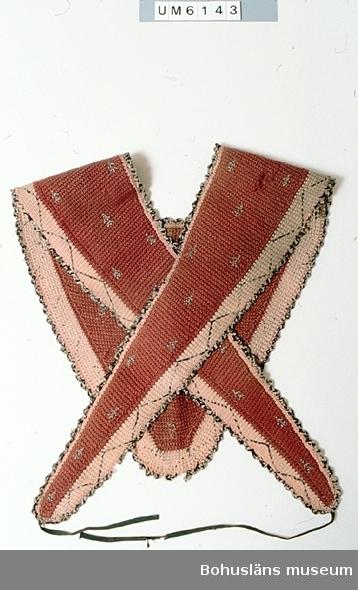 Schal för kvinna av ull, virkad i tunisisk virkning = krokning (se litteraturen). Lägges på axlarna med en trekantigt formad bit bak som täcker övre delen av ryggen och två långa snibbar fram, som lägges omlott över bröstet och dras bakåt för att knytas i midjan. Schalen är brun med en gulrosa bård längs ytterkanterna. På det bruna partiet finns spridda mönster och på bården sicksack-mönster broderade i kedjestygn med svart/vitt-melerat garn. Längs kanterna en virkad  udd av samma garn. Nederst på snibbarna finns påsydda knytband av svart ylleband. Tillverkningstiden är osäker. Enligt litteraturen förekom mönster på  tunisisk virkning från mitten av 1870-talet till och med 1920-talet  i mönstertidningar och virkböcker. Dateringen gjord utifrån de uppgifterna. Två hål i det bruna partiet. Uddkanten bortsliten på flera ställen. Knytbandet trasigt. Smutsig. Blekt. Litt; Paludan, Lis, Haekling Historie og teknik, Gylling 1986, sid. 618 24-25, 106-115, 274-277.  Widhja, Inger, Takhimlar och brudhandskar textil tradition i Västergötland, Skara 1990, sid. 109. Fanns inte vid inventering 1934 men vid inventering 1958.  Ur Nationalencyklopedin: Ami kallades under 1800-talet en lång sjal, vilken lades runt kroppen på liknande sätt som det prästerliga halslinet. Amin värmde speciellt axlar, korsrygg och bål (den har ibland även kallats hjärtevärmare) och användes av kvinnor i utomhusarbete. - Ordet kommer av fr. amict, eg. 'halslin', och har senare associerats med fr. ami 'vän'.  Ur handskrivna katalogen 1957-1958: Virkad schal Med nedhängande snibb och knytband. Totallängd c:a 122,5 cm. Röd med broderi i svart och vitt. Smärre hål.
