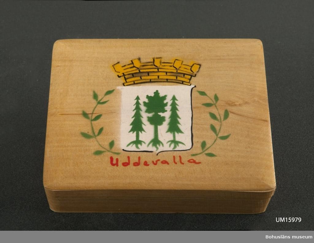 """Rektangulärt. På locket målat namnet """"Uddevalla"""" samt dess stadsvapen. Troligen tillverkad på 1950-talet.  Se UM015810"""