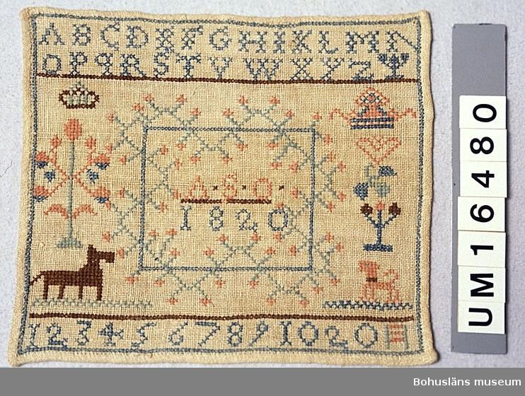 """Rektangulär märkduk av tuskaftvävt linne broderad med lintråd och ev bomullstråd till vissa delar. Överst alfabetet, nederst siffror, i mitten en ruta omgiven av stili- serade blommor med texten """"ASO 1820"""", vid sidorna djur, hjärta, krona m fl små-motiv. Har ägts av läderhandlare Johan Teodor Wallgren, Höjentorp, Uddevalla f 1849 och hans hustru Olena född i Bäve socken 1842. Givaren är född Wallgren. Bottenväven gulnad.  Litteratur: Landergren, Karin, Märkdukar ur Kulturen 1941 sid. 83-102. Kjellberg, Anne. Navnedukar. C. Huitfeldt forlag 1985. Rosenknopp och yllestopp, utställningskatalog från Helsingfors Stadsmuseum 1986, sid. 11-15."""