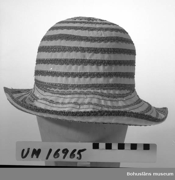 Tillverkad av två slags ripsband, ett blått med uddkant och ett rakt vitt. Dessa sydda spiralvis från kullens topp och nedåt utåt. Se UM16935.