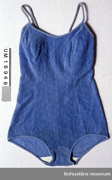 Föremålet visas i basutställningen Kustland,  Bohusläns museum, Uddevalla.  503 Kön KVINNA  Ljusblå baddräkt av stretchfrotté (trikå) med ytmönster av romber. Sydd av tre våder fram och två bak. Rundad ringning fram. V-ringad till en bit ovanför midjan bak. Kantad med stretchfrotte utan ytmönster vid benen, armhålen och upptill. Smala fasta axelband av samma tyg. Fodrad med ljusblå syntettrikå vid bysten och vit bomullstrikå i grenen. Något sliten. Fodret i grenen har lossnat på en bit. Små rostfläckar på ena axelbandet. Hängande trådändar vid axelbanden.  Litt; Larsson, Marianne, Från badkostym till bikini ur Fataburen 1988, sid. 136-160.  Rowland-Warne, L, Fakta i närbild Kläder , Bonniers Juniorförlag AB Stockholm 1993, sid. 34-35. Omkatalogiserat 1997-09-30 VBT
