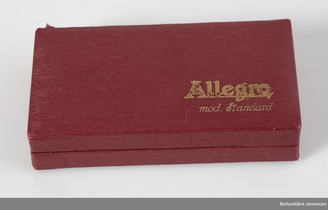 """Slipapparaten """"Allegro, mod. Standard"""" för rakblad, tillverkad i Schweiz. Förvaras i originalsk UM020412:2, utförd i röd, läderimiterande formpressad papp med guldskrift. På lockets insida bruksanvisning med bilder. I asken även lös bruksanvisning.  Personuppgifter om givaren, se UM020411. Se bilaga."""
