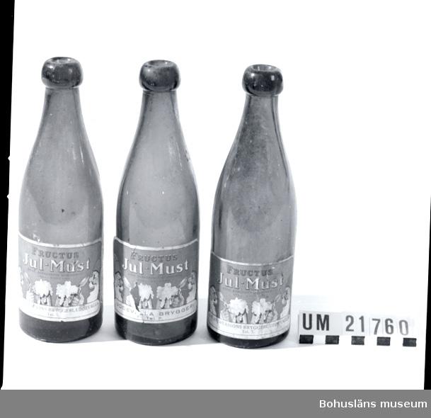 """Föremålet visas i basutställningen Uddevalla genom tiderna, Bohusläns museum, Uddevalla.  410 Mått/Vikt ! 0,37 KG, DIAM 3 CM 594 Landskap BOHUSLÄN 394 Landskap VÄSTERGÖTLAND  Brunt glas med mynning för naturkork. Etikett med tomtar och ölsejdlar.  Märkt: """"Fructus Jul-must, mörk bornerade Bordsdryck lagl. Skyddad. Uddevalla Bryggeri. Tel: 7."""" Flaskan tillverkad på Limmareds glasbruk, Älvsborgs län, Tranemo sn, Södra Åsarp.  UMFF 49:4."""