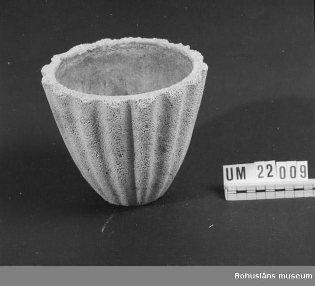 """Blomkruka, gjuten av korallkalksten och cement. Krukans utsida har vertikala vågformer. Ytan är ljust beige, troligen materialblandningens naturliga färg.  Gjutna blomkrukor av korallkalksten och cement var keramikfabrikens stora 1940-talsprodukt. Kalkstenen importerades från Danmark. Bl. a. gjorde Statens Järnvägar en stor beställning på en större fristående modell avsedd för blomsterarrangemang utanför stationerna.  På Syco AB tillverkades servis- och prydnadsgods mellan åren 1946 - 1968. De sista sju åren drevs fabriken under namnet Nya Syco AB. Ledare för företaget då var Åke Johansson, sedemera Jaking, Strömstad/Trollhättan. (Intervjunr 361 i museets arkiv.) Företagets namn kom troligen från den danska firman Syberg Olsen & Co, vilka hade ursprungspatentet till den blandning som de populära Syco-blomkrukorna gjordes av. Ytterligare upplysningar under Arkivbildarnummer 193 i museets arkiv.  Litteratur: Artikel i Strömstads tidning den 15 november 1952, Slut på Sycos leksaker nyttokeramik i stället; artikel i Halden Arbeiderblad den 7 april 1993; Bohuslän Årsbok 2000, Föremål och dokumentation, artikel """"SYCO - bohuslänskt bidrag till svensk keramikhistoria"""", Stellan Granat, sid 55-62."""