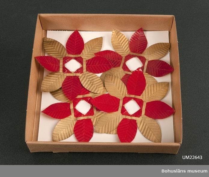 594 Landskap BOHUSLÄN  Ljusmanschett föreställande julros med åtta blad. 4 i rött, 4 i guldfärg  UMFF 128:3