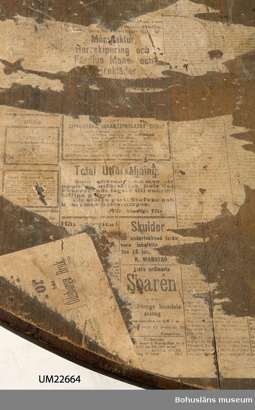 """594 Landskap BOHUSLÄN  Två lösa halvrunda delar, vardera på tresidig underdel med tre ben. Målad träådring i brun/svart. Bordsskivan skadad. Fragment av dagstidningar har fastnat på 3/4 av bordsytan, på den fjärde delen har rest av undersidan på ett mörkt vaxduksliknande material fastnat. Blyertsanteckning på ena bordsskivans undersida: """"Alfred Johansson den 3 april 1888 Mycken snö ligger"""".  Bordet har använts som förebild till nya bord i del av Museikaféet år 1999, samt som förebild till nya bord i personalrummet år 2000. I båda fallen har beställningarna gjorts från Lotsarnas Träverkstad HB i Uddevalla (Göte Hurtig)."""