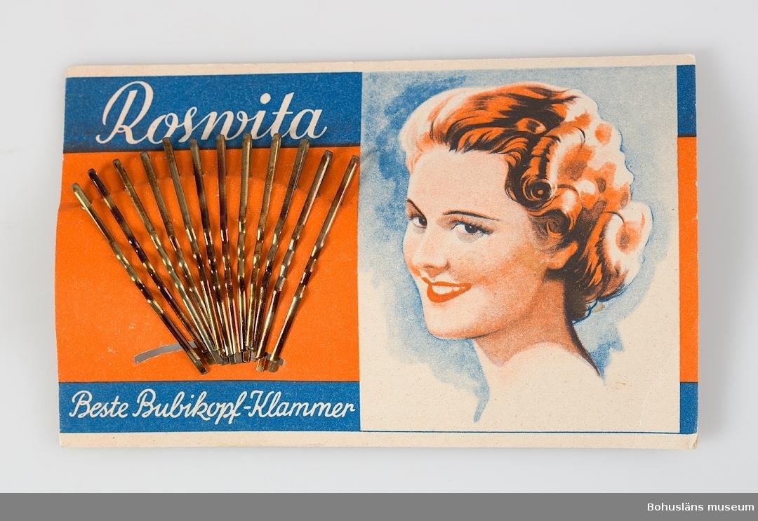 """Rektangulär, pappskiva med dekor i rött, blått, vitt och text: """"Rosvita. Beste Bubikopf-Klammer."""" 12 hårnålar av mässing isatta i solfjädersformat. Tre kartor, en skadad."""
