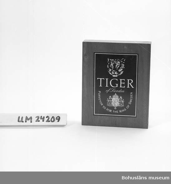 """Träblock med en påklistrad logotyp, text: """"TIGER of Sweden PURVEYOR  TO H.M. THE KING OF SWEDEN. Det finns en liten svart klisterlapp med vit text på ena kortsidan: """"PEETZ & DUJARDIN DK-2830 VIRUM"""". Kan  eventuellt vara tillverkaren."""