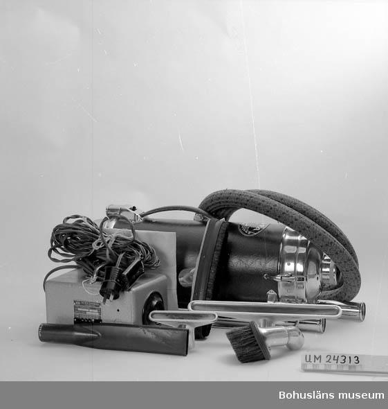 """471 Tillverkningstid 1930-TAL?  Dammsugare i 12 delar: 1. Dammsugare. Vinröd och svart syntet-klädsel. Krom på kortsidorna. Står på skenor (kromade). Läderhandtag. Sladduttag och strömbrytare vid handtaget. Ovalt metallmärke på ovansidan, text: """"VOLTA, 8S/108586 105 - 115 = 250 watt"""". 2. Transformator. Grå metallåda med handtag och brun sladd. 3. Sladd. Brun plast. 4. Rör, metall. 5. Rör, metall. 6. Sugslang. Klädd med textil (röd, svart, beige). Metall i ändarna. 7. Fogmunstycke, plastmaterial, svart. 8. Möbelmunstycke, metall. 9. Borstmunstycke, 2 delar, metall. 10. Golvmunstycke, trä, gummikanter. 11. Golvmunstycke, metall 12. Filter. Beige bomullsflanell. Ligger i papperspåse från ÖSTRAS"""