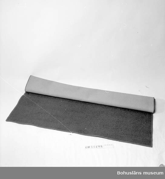 Slät matta, öglevävd på gummibotten, vars undersida har ett reliefmönster av rutor. Langetterad runt alla fyra sidorna.  Kraftigt grön, något melerad färg, typisk för 1960- och början av 1970-talet. Personuppgifter och fakta kring samlingen se UM025572.