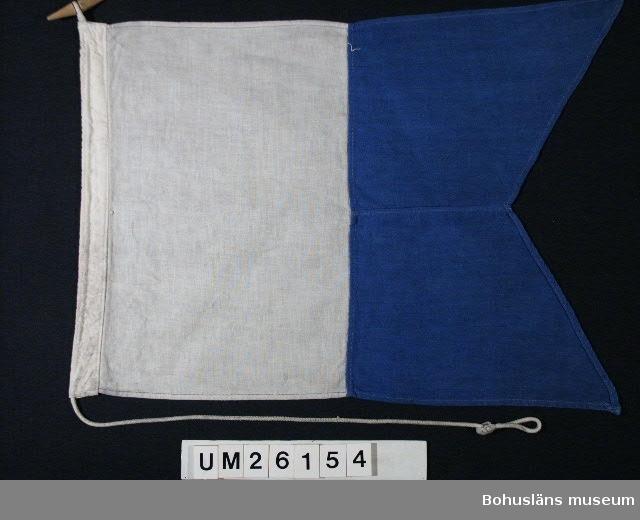 """Två fält, det inre vitt, det yttre  med två tungor blått.   Betyder: """"Jag har dykare nere. Håll väl undan och gå med sakta fart"""". Användning se UM026139  Personuppgifter se UM026024"""