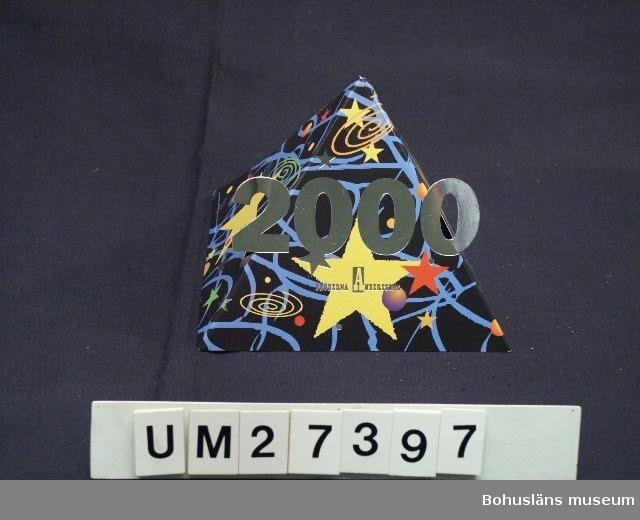 Jul -och nyårshälsning till  Gregarts möbler i Uddevalla från Bröderna Anderssons industrier i form av en papperspyramid  - tetra - med färgtryck på utsidan . Delvis utvikbar form på framsidan med siffrorna 2000 i silver mot en bakgrund av fyrverkerier i många färger på en svart himmel. Hälsningstext samt undertecknat på insidan.  För information om Millennieinsamlingen, se UM2736