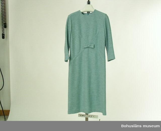 """Föremålet visas i basutställningen Uddevalla genom tiderna, Bohusläns museum, Uddevalla.  Turkosmelerad klänning  med halvlång ärm i mjukt, ylleliknande tyg. Rund, enkel halsringning, lång dragkedja i ryggen. Framstycket ihopsytt av fyra kilformade delar som möts strax under bystmitten. Dekorsöm markerar denna skärning. Skärningen dold av en rosett i samma tyg. Bystveck och insparningar i ryggen. Två vertikala och en längsgående insparningar i ärmen för bättre passform.  Mittsöm bak. Fodrad med tyg i acetat i turkos. Etikett i halslinningen med med texten: """"Magnita 40"""".    I dragkedjan vidhängande pappersetikett i silkessnöre med texten: """"Magnita  Modell  Varudekl Modell  A 39 Kval. 524 Färg  4 Storlek  40 Pris Vid platsen för pris har Prylmarknaden fäst en klisterlapp med texten """"Kr 45.-""""  Denna klänning är """"à la Jaqueline Kennedy"""", som var en av 1960-talet förebilder inom modevärlden. Obegagnad vid förvärv.  Ur Nationalencyklopedin, NE.se: Terylen  Terylen, skrynkelhärdig textilfiber framställd av polyester ursprungligen varumärke, sedan 1955; av eng. terylene med samma bet.   För ytterligare uppgifter om förvärvet och övrigt material rörande Magnafabriken i museets samlingar, bl.a. dokumentation 1998, se UM027416."""