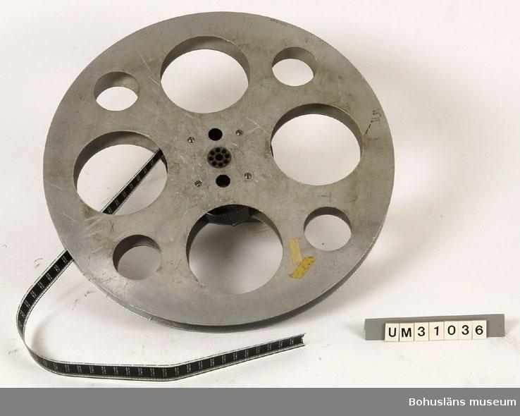 """Filmspole med filmen """"Nästa program på denna teater"""".  Filmen sitter i filmprojektor UM31031.  Projektorn är tillverkad av AEG på 1920-talet och har använts i Folkets Hus i Sjöbol vid Lysekil.  Till projektorn hör en lång rad delar och olika tillbehör, UM31031 - UM31062.  För ytterligare upplysningar om filmprojektorn, dess olika delar och användning, se UM31031."""