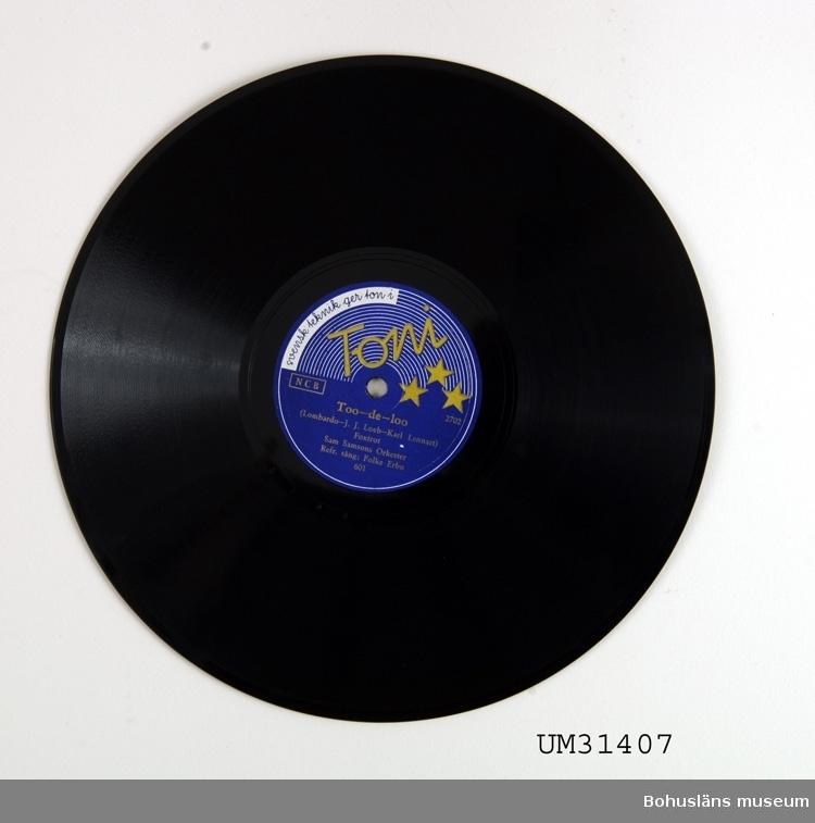 """Grammofonskiva, stenkaka i papperfodral. Märkt """"Abrahamson"""". Ena sidan: När du gick. Foxtrot. Sam Samsons Orkester. Andra sidan: Too - de - loo. Foxtrot. Sam Samsons Orkester. Skivmärke: Toni  Grammofonskivan som ingår i skivsamling som spelats i en sommarstuga i Sundsandvik, byggd 1939. Skivorna spelades på en svart resegrammofon, se motsvarande modell UM026268. För ytterligare upplysningar om förvärvet, se UM031385."""