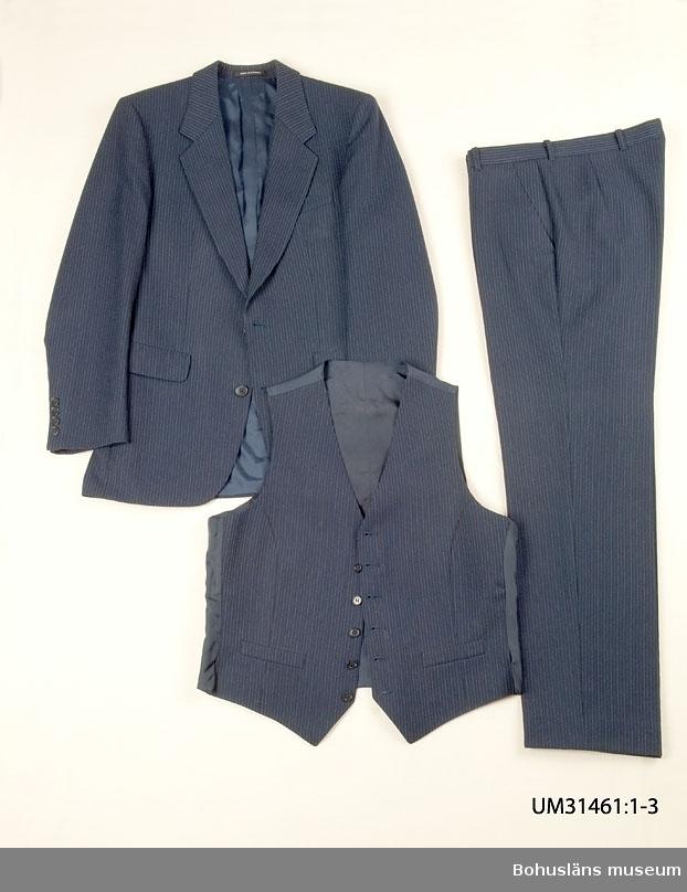"""Mörkblå kostymbyxa (UM31461:1) sammanhörande med kostymkavaj (UM31461:1) och kostymväst (UM31461:3). 410 Mått/Vikt  Benlängd 79 cm  Benvidd 21 cm  Kostymbyxa i mörklblå ull med smala kritstreck. Ofodrade. Linning med hällor för bälte, knäpp framtill med slejf. Gylf med dragkedja, Två snedställda sidfickor, en infälld bakficka med dekorknapp. Fickor av vitt bomullstyg.  På insidan firmaetikett med texten: """"TIGER OF SWEDEN STORL. SIZE. GRÖSSE  B 48. 451 26 UDDEVALLA På baksidan uppgifter om kvalitet och tvättråd."""