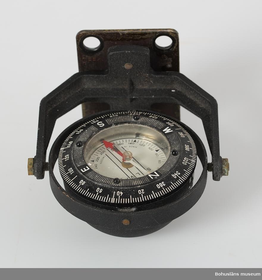 Kardanupphängd kompass av märket Silva marinkompass i kompasslåda av ek med skjutlock. Tillhörande uppfästningsplatta. I lådan tryckt monteringsanvisning samt instruktioner för kurstagning och transport i text och teckningar, I lådan också en miniräknare och en kontakt med oklar användning. Lådan är för liten för kompassen.