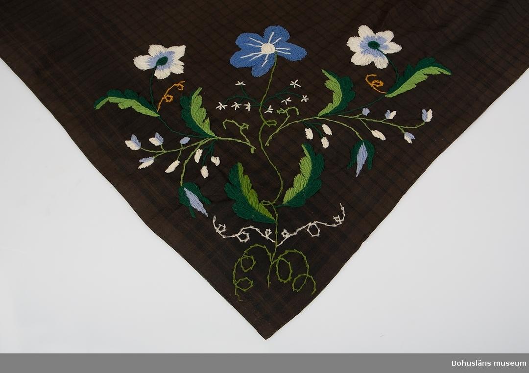 Rutmönstrad bomullsschal, troligen hemvävd. Schalen är senare överfärgad i brunt och pryds med kraftiga yllebroderier av blomstergirlander i två av schalens motsatta hörnen. I ena hörnet är blommorna kulörta, i den andra är de svarta, möjligen för högtids- och vardagsbruk. Vikningar på diagonalen efter bruk och blekskador. Schalen har varit mest använd på den svartbroderade sidan.