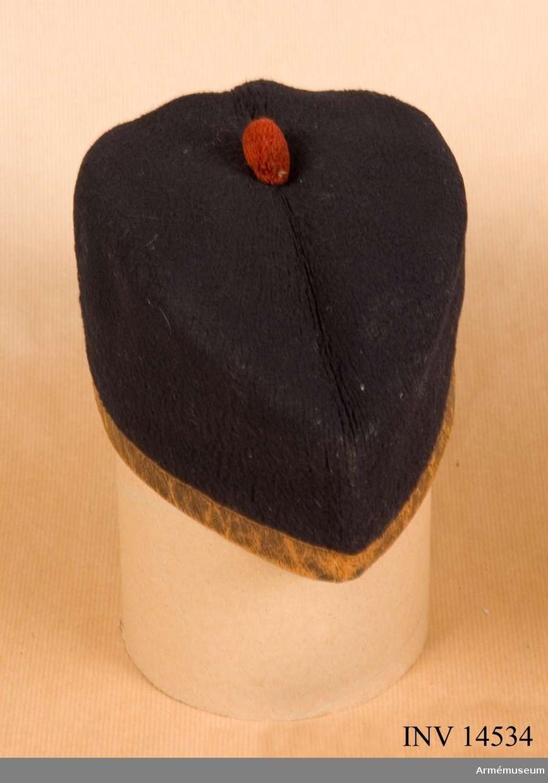 """Grupp C:I. Skotskmössan (Glencarry cap) av svart-blått kläde med läderband (2 cm breda) vid nedre kanten. Vid mössans baksida två lösa band 3 cm breda och 16 cm långa. På mössans kulle en pompon av rött ylle. Foder av svart bomullstyg med stämlar: """"W 8 (en uppåtriktad pil) D"""" och """"22"""". Litteratur: Die Englische Armé. Leipzig. Verlag von M. Ruhl. sid 21. Mössan användes för dagsuniformen och är av svart kläde. Mössan på engelska: """"Glencarry Cap"""". Senare  linjeinfanteriregementen använda sådana mössor utan vit-rött band. Skotska regementena behålla detta band på sina mössor. Arméns Album: II band. Die Englische Armée, Leipzig. Vorlag von M Ruhl. Bilder med linjeinfanteriregementens uniformer med samma mössor utan röd-vitt band vid nedre kanten. Die Heere und Flotten der Gegenwart Grossbritanien und Irland. G von Zepelin. Leipzig 1897 sid 34. På 1800-talets slut fingo linjeinfanteriregementena fältmössor av blått kläde liknande Österrikes men utan skärm; skotska regementen bibehålla sina nationalmössor """"Glenncarry"""". Handbuch der uniformkunde. Prof. R Knötel, Hamburg 1937. Sid 197. Tjänstemössorna voro först från 1815-1860 av mjukt mörkblått kläde, tallriksmodell; senare båtsmodell av samma kläde."""