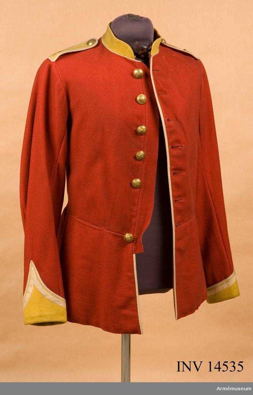 """Grupp C:I. Vapenrock av rött kläde, 70 cm lång, enradig med sju knappar (fyra saknas), åtsittande med tvärsöm i midjan. På vänster sida vid midjan mässingskrok för livrem. Längs knäppningarna på bröstet ochpå ryggen vid båda sömmarna (nedre del) vit tjock passpoil. Axelklaffar av gult kläde, med rött underkläde och med bred, vit passpoil omkring; axelklaffar fastsydda i ärmsömmen och fastknäppta med en mässingsknapp. Axelklaffarna försedda med nummer """"9"""" av mässing, regementsnummer. Foder av vitt ylletyg och ärmarna av vitt linne. På klädets nedre del fastklistrad en liten bit papper, resten av en etikett. Knappar av mässing, 2 cm i diameter med ingraverad krona och nummer """"9"""" (regementets nummer) sju st på framsidan (en saknas) och två flata knappar av mässing på axelklaffarna. Krage upprättstående av gult kläde, 4 cm hög, med vit passpoil vid nedre kanten. Kragen har hyska och hake och rött underkläde. Ärmuppslag i vinkelform av gult kläde med vit bomullsbord och vit passpoil omkring. Litteratur: Handbuch der Uniformkunde. Prof. Rickard Knötel. Hamburg 1937. Sid 196. År 1815 blevo för alla regementen, klädernas kännetecknande färg oförändrad. Efter år 1881 förlorade alla regementen sin numrering och fingo i stället endast sitt namn efter rekryteringsdistriktets benämning. Sid 199. """"Norfolk Regement"""" - gamla nummer """"9""""."""