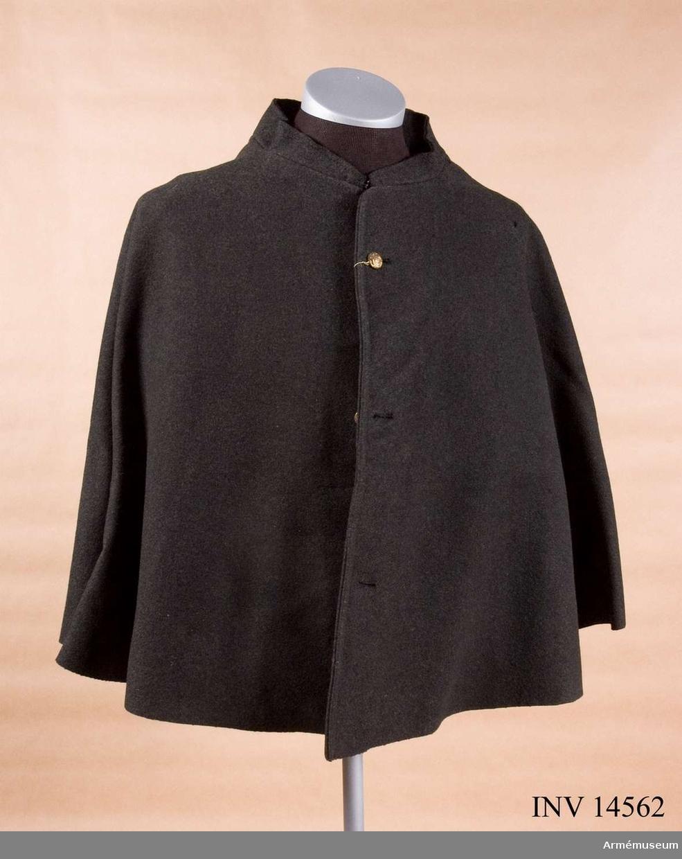 """Grupp C I. Kappkrage av mörkgrått kläde, 53 cm lång, enradig med tre knappar. På klädets insida är en papperslapp (firmaetikett) med påskrift fastklistrad: """"Limerick Army Glathing Company limited"""" (Limerick Armé Beklädnads AB) """"1879 Pt In"""" Bokstäver """"W10P"""" och """"660 5 M 9"""". Knappar, på bröstet, tre st, 1,7 cm i diameter av guldfärgad metall med engelska statsvapnet. Krage  upprättstående, med hyska och hake. Kappkragen användes vid kyla och regnväder för uteposteringar."""