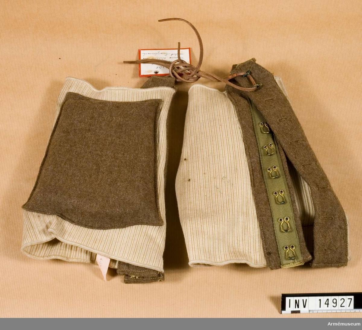 """Grupp C I Av starkt bomullstyg. Remsa av khakityg med mässingshyskor och knapphål som stänges med lädersnören. På skyddens yttre sidor finns fyrkantiga dynor, som på ena sidan är klädda med kläde och på den andra med bomullstyg. Etikett av bomullstyg med påskrift """"Everlastic Size 2 1945"""" med uppåtgående pil mellan c och S. Används vid hopp från flygmaskin."""