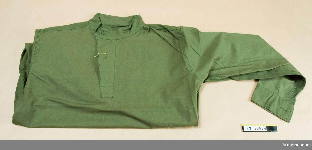 Flanellskjorta m/1959.Grupp C I.Ingår i fältuniform m/1939 bestående av vapenrock, fältbyxor, flanellskjorta, halsduk av bomull, skodon, gummipjäxor.Gåva från Arméintendenturförvaltningen.Inventerad 1971.