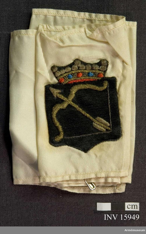 Grupp C I. Armbindel för officer som deltagit i frihetskriget 1918 i Finland, Satakunta. Armbindel - en vit 10 cm bred armbindel av siden med broderat Savolax vapen (bågen) med treuddig krona.