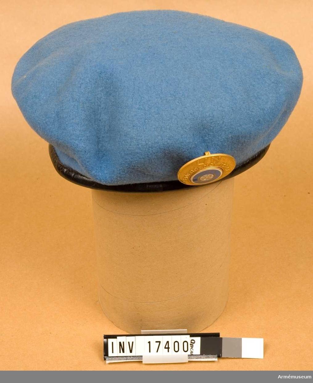 """Grupp C I. Basker, för trupp ur Förenta Nationernas övervakningskommission vid Suez och Gaza-remsan i Egypten 1956-67. Av ljusblått kläde med svart kant (svettrem) av skinn. På vänstra sidan ett emblem av emaljerad gulmetall med text: """"UN EMERGENCY FORGE United Nations Nations Unies"""". Foder av svart bomullstyg med märkning: """"Fleur de Lis BERET 6 7/8  Dorothea Knitting Mills LIMITED TORONTO"""".  Beskrivning 1973 S W-ge."""