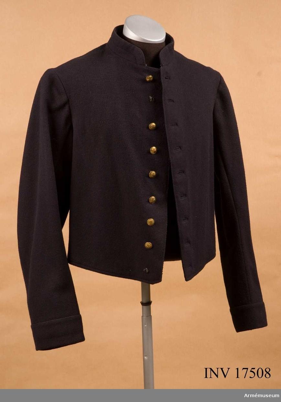 """Grupp C I. Jacka (veste) av mörkblått kläde, 50 cm lång. Rocken är enradig med 9 knappar. På rockens vänstra baksida finns en ögla (för livrem) av kläde med läderfoder, försedd  med knapp. Fodret är av vitt tyg med löst påsatt innerficka. På fodret finns det några stämplar: 1) """"7.7.1899 G.T. Commission"""" ..., 2) en liten stämpel som är oläslig och 3) """"56"""" troligen avseende storleken. Knapparna är av mässing, diameter 1,7 cm, med en flammande granat. Kragen är uppåtstående, 3,5 cm hög, av samma blå kläde, med hyska och hake. Även fodret är av samma kläde. Ärmupslagen är raka, 6 cm höga. LITT  Arméenalbum II Frankreich. Die Französische Armée in ihrer  Uniformierung vor dem Weltkriege (första). Leipzig. M. Ruhl  Copyright 1937, sid. 20 Infanterie. """"Für Exercis und  Arbeitsanzug"""" - Jackliknande klädespersedel av mörkblått kläde med krage och ärmuppslag av samma tyg. Klaffarna på kragen är av rött kläde med regementsnummer och axelklaffar. Allt detta saknas. På """"veste"""" finns nio små knappar med flammande granater av guldfärgad metall, som är infanterikännetecken. Handbuch der Uniformkunde, Prof Rich. Knötel, Hamburg 1937, sidan 160, 1871-1915. Infanteriet har tre olika kläder:  1) vapenrock, 2) exerciskläder """"veste"""" - blå jacka med smal krage och axelklaffar. På kragen röda klaffar med regementsnummer. Allt detta saknas. 3) kappa. Collection complete des tracés de coupe des Effets d'Habittement. Ministere de la Guerre 1845-47 plansch 2 """"Veste"""" - infanteri de ligne. Ritningar och mått på """"veste"""" - delar."""