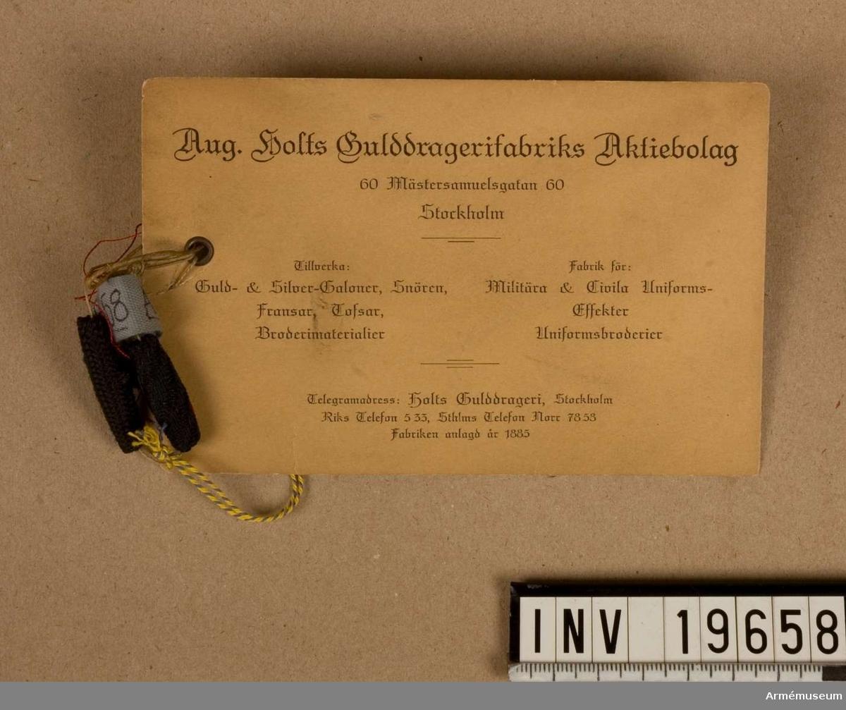 """Knapparna är flätade på olika sätt. Den ena är något längre och smalare än den andra. Båda är svarta. På den tillhörande etiketten fr. Aug. Holts Gulddragerifabriks Aktiebolag, står det, handskrivet: """"Knappar nålade."""" August Holts Gulddragerifabriks Aktiebolag grundades 1885. 1906 sattes företaget i likvidation, men nyregistererades 1909. Till 1983 försåg företaget framförallt militären med tofsar och band vävda av guldtråd i någon form. Men alltfler av militärens order lades utomlands, i Asien, där produktionen var billigare. Aug. Holts Gulddragerifabriks AB fick svårt att klara konkurrensen, trots att deras varor höll högre kvalité än de importerade. När firman upphörde 1983 fick Nordiska museet en stor del av lagret. De kontaktade Armémuseum. Irma Wallenborg och Gunvor Klingberg fick välja ut material med militär anknytning. Huvuddelen av samlingen finns dock fortfarande i Nordiska museet."""
