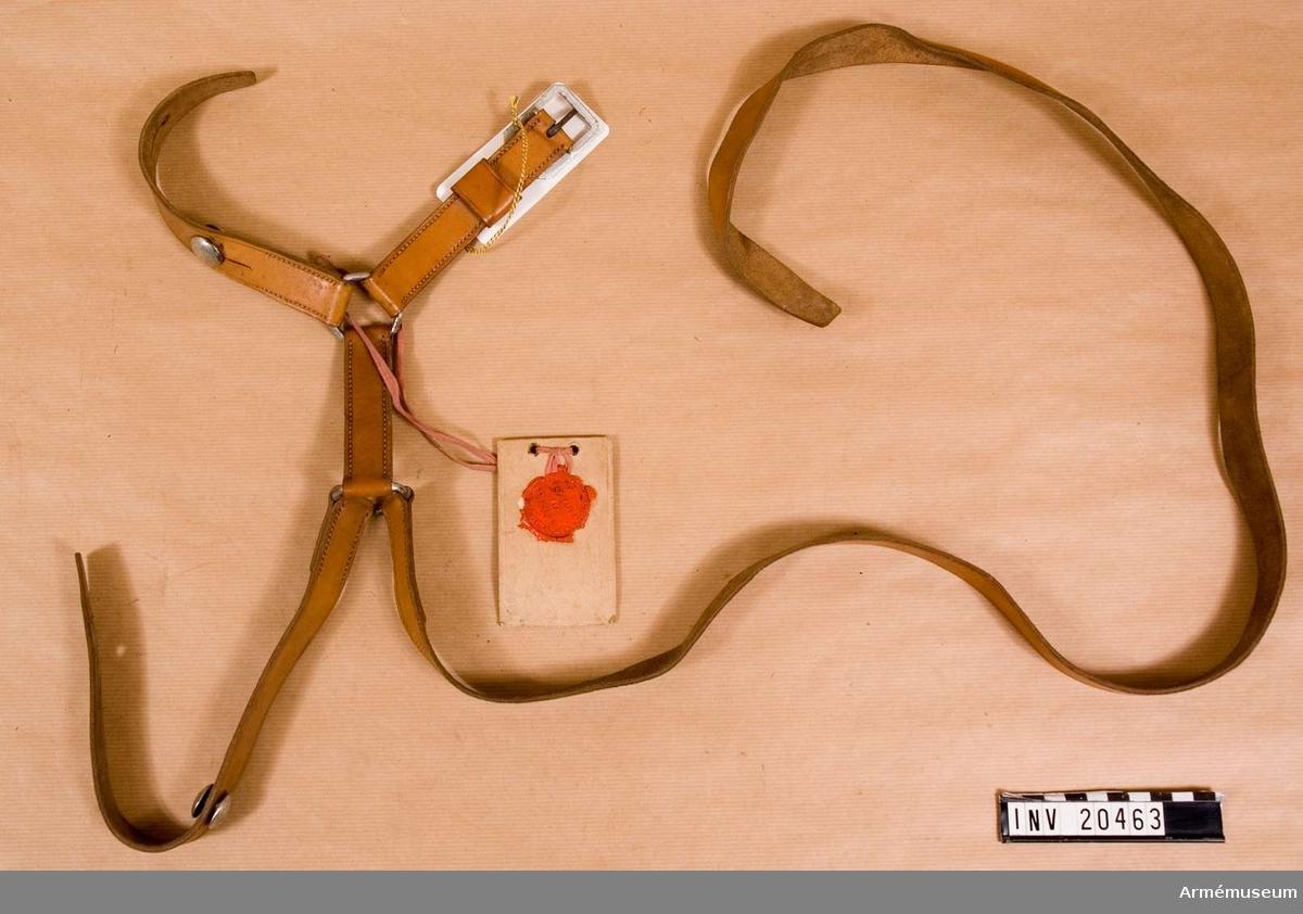"""Grupp C I. Av brunt läder. Med spänne för längdreglering av remmen. I ändarna två ringar med remmar vid vilka sabeln fästes. Två remmar med två knapphål och knappar med vilka sabeln fästes vid gehänget. På axelremmen finns en stämpel, på vilken det står på ryska """"T. G. Kurikoff"""" namn på fabriksägaren. Detta gehäng infördes vid ryska kavalleriet samtidigt som dragonsabeln m/1881. En etikett med fransk text på den ena sidan: """"Postesabre de cavallriie""""; på svenska """"Kavallerigehäng"""". På den andra sidan finns ett runt sigill med rysk text  för """"Modellsigill"""". Omkring sigillet rysk text, sv. """"Tekniska kommittén, intendenturens huvudförvaltning""""."""