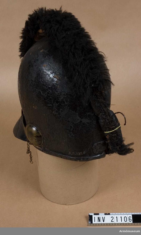 Grupp C I. Av lackerat svart läder med stor framskärm. Baktill en rem med reglerspänne. Alla metalldelar är av mässing.  Foder av läder och grov linnelärft. På framsidan av hjälmen kättingar (trasiga) samt ett 2 cm brett band av mässing. Tagelliggaren är fastsydd vid hjälmen. Baktill en svart fårskinnskant, och på vänster sida en rosett. 1798-1806.