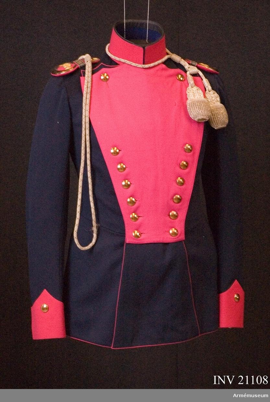 """Grupp C I. Ur uniform för officer vid 10 Ulanerregementet, Tyskland. Består av vapenrock, epåletter, långbyxor, ulanmössa, pompong, tagelplym, älgiljett, skärp, banbolärrem, kartuschlåda och rem, stövlar, sporrar. Buren av Obernitz. Av mörkblått kläde. Åtsittande med midjesöm. Tvåradig med 12 knappar. Båda bakfickorna Båda bakfickorna har ett treuddigt lock, vardera med 3 knappar, två knappar bak i midjan. Epålettslejf, galon b:20 mm, med karmosin rött underkläde. Bredvid epålettslejfen finns en fastsydd knapp. Foder av svart siden med innerficka. På framsidan finns ett bälte av av samma tyg med hyska och hake av vitmetall. Fodret på bröstet är av rött kläde. På innerfickan finns en fastsydd etikett """"A.Berger Jun. Kgl.prinzen hoflieferant. Potsdam Höke- weg str. 1-2. Löjt. V.Obernitz. 8.5.13"""". Knappar kopparfärgade, d:20 mm. Krage upprättstående med raka vinklar av rött kläde, med svart passpoil på kragens övre kant samt 3 hyskor och hakar. Kragen är fodrad med svart tyg. Passpoiler röda längs rockens främre och nedre kant, samt alla rygg-, fick- och ärmsömmar. LITT  Das Deutsche Reichsheer. G Krickel. Berlin. Sida 105. Ägiljett för officerare vid ulanregementet blev införd efter dagorder 17 september 1822 och 18 december 1878. Bekleidungs-Vorschrift. Uniformenkunde Das Deutsche Heer. Her. Knötel, band II.Enl W Granberg."""