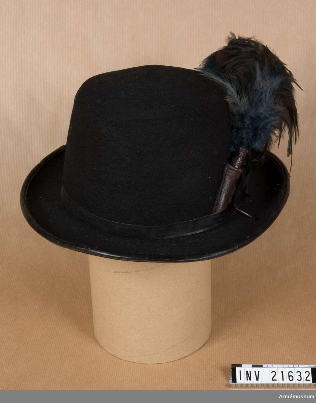 """Grupp C I. Hatt av svart vattentät filt. Består av huva, brätte, band av svart läder, rund, nedre del och på V sida en läder hållare fjäderbuske av svarta och blå- gröna tuppfjädrar. Foder av en halvrund tygbit på hattens botten på vilket det står """"2"""". Inne, omkring hatten, svettrem med 2 hål för hakrem; endast en liten bit kvar av hakrem och utan spännen. LITT  Adjustierungs und Ausrüstungs Vorschrift für das K.K. Heer III Theil. Wien 1871. Sida 128 Jägartruppe. Hut. Fullständig beskrivning på jägarhatt med ritningar.Handbuch der Uniformkunde. Rich. Knötel, Hamburg 1937. Sid 272. Jäger und Schützen. Denna jägarhatt har flera gånger föränd- rats. Ritning på sida 271. Abc 108 i, k, l, - i olika tider jägarhattar.Armeenalbum III. Uniformen. Distinktions und sonstige Abzeichen des gesuntere Österreich-Ungarischen Wehrmacht. Oberst M Judex, Leipzig. 1908. Sid. 14. Jäger. Mannschaft. Hut - kort beskrivning. Bilaga sida 9 uniform i färger: för olika jägartrupper och sida 17 landwehrtrupper."""