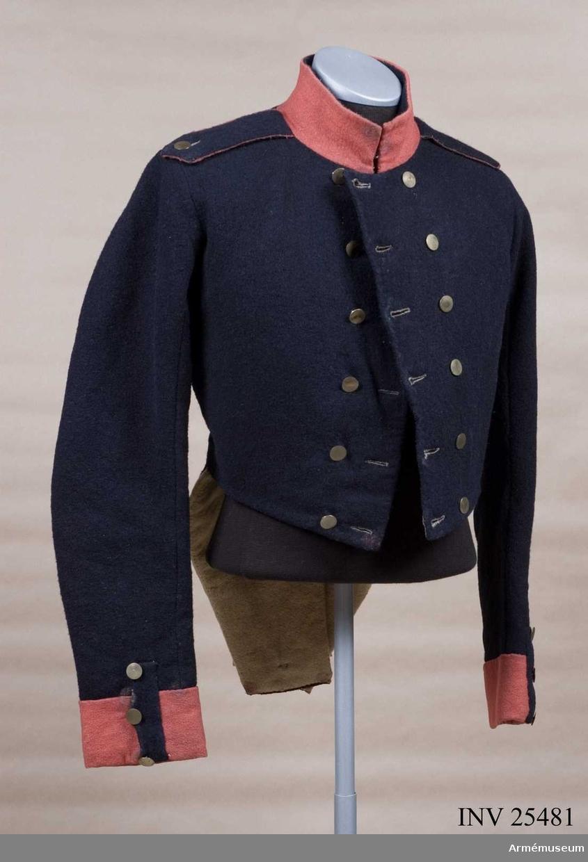 Grupp C I. Ur uniform för manskap vid indelta infanteriet; 1816-1829. Består av jacka, byxa, tschakå, pompong, kordong, vapenplåt, skärp, halsduk, patronkök, bandolärrem, skor, damasker, bajonettbalja. Jackan är modellexemplar. Go 1/3 1816. Lacksigill på fickans insida.