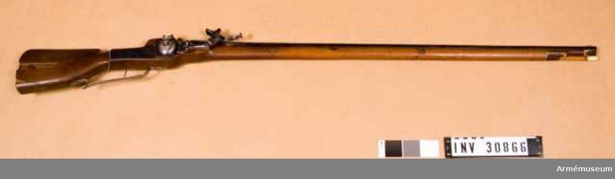 """Grupp E XIV.  Pipan är blånad. Det 31 cm långa, åttkantiga kammarstycket avgränsas framtill med en smal upphöjd rand eller fals. Det långa fältet har cirkelrund genomskärning. Ett med bred siktbalk och 2 cm lång framåtriktad fot försett ståndsikte är inlaxat i pipan 13 cm framför dennas bakände. Ett pärlkorn av mässing sitter 0,8 cm bakom pipmynningen. Litet framför bakänden finns på kammarstyckets övre högra och vänstra kant ett tvärgående, kedjeliknande ornament, som på vardera sidan omgives av ett par ingraverade ränder. Framför dessa ornament är på den högra kanten ingraverat D och på den vänstra M. På pipans vänstra sida är nummer 11 inslaget. Pipan har inga andra stämplar eller märken. Pipan fasthålles i stocken med en nedifrån insatt korsskruv och med tre häften.  Låset har platt, blånat bleck och blank hjulbuckla. Hanen har rörlig underläpp. Fängpannelocket stänges automatiskt, om man trycker på en hjulbucklan och hanen befintlig knapp. Den inre låsmekanismen är av vanlig typ. Det finns dock en egendomlig säkerhetsmekanism, bestående av en smal stång, som är placerad horisontalt på studelns insida, och som framtill är böjd i två vinklar, så att stångens främre del ligger an mot låsblecket. I bakänden har stången en nedåtriktad arm eller klack, som nu ligger an mot avtryckarestången, men som sannolikt ursprungligen legat bakom denna.   Säkringsstången är fäst vid studeln och rörlig kring en skruv, som sitter ungefär 5 cm bakom stångens framände. Säkringsstångens främre del tryckes uppåt av en fjäder, som med en skruv är fäst vid studeln. Hanaxeln har på låsbleckets insida en sorts nöt, som har en ganska lång, bakåtriktad tand. När hanen fälles """"på"""", d v s bakåt, trycker den sistnämnda tanden stångens främre del nedåt, varigenom klacken på säkringsstångens bakände lyftes upp från och släpper avtryckarestången. Låset har enkel avtryckare.  Bössan har helstock av gult trä. Kolven är """"fransk"""" men med kindstöd. Till det sistnämnda finns längs fram ett inskuret orn"""
