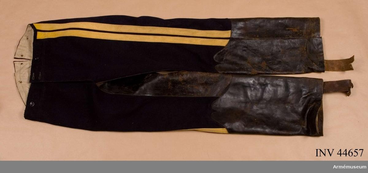 Samhörande nr är 44656-64, uniformspersedlar. Grupp C I.  Uniform för manskap vid Wendes artilleriregemente, 1830-45,  bestående av dolma, byxor, kask, skor, knutskärp, kartusch med rem, halsduk, sabelkoppel och sabelhandrem. Byxor i mörkblått kläde med två gula lister i sidorna, grenskinn och stövelskoning samt fodrade med grått linne. Hällor av läder. G.o. 25/10 1830 Wendes artilleriregemente.