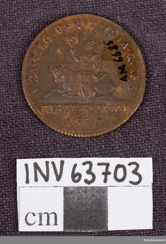 """Grupp M. Medalj graverad för Arvid Karlstens 2:a regentlängd. Åtsidan: """"CAROLUS. XII. D. G. REX. SVE"""". Bröstbilden föreställande Karl XII åt höger i peruk, harnesk och mantelveck. Frånsidan: A.CAROLO. VENIT. ISTA.QVIES. En kvinna (Europa) med tornkrona på huvudet och olivkvist i handen sitter på en liggande axe. I avskärningen PARTA RVSVICI 1697. Medaljens kant är på båda sidor strierad."""